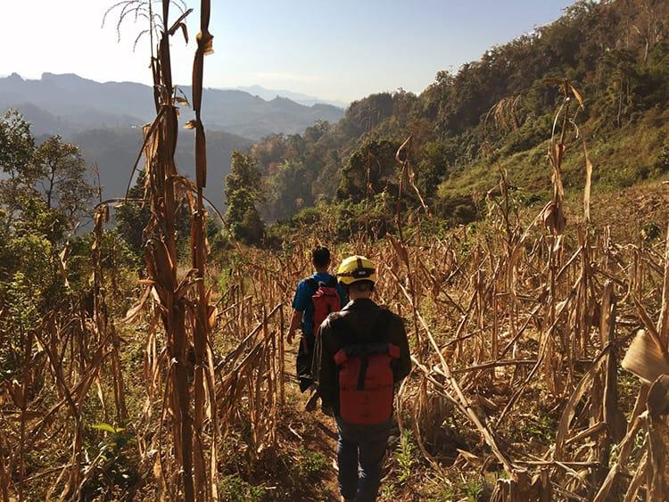 A guide and trekker walk through a field in Thailand
