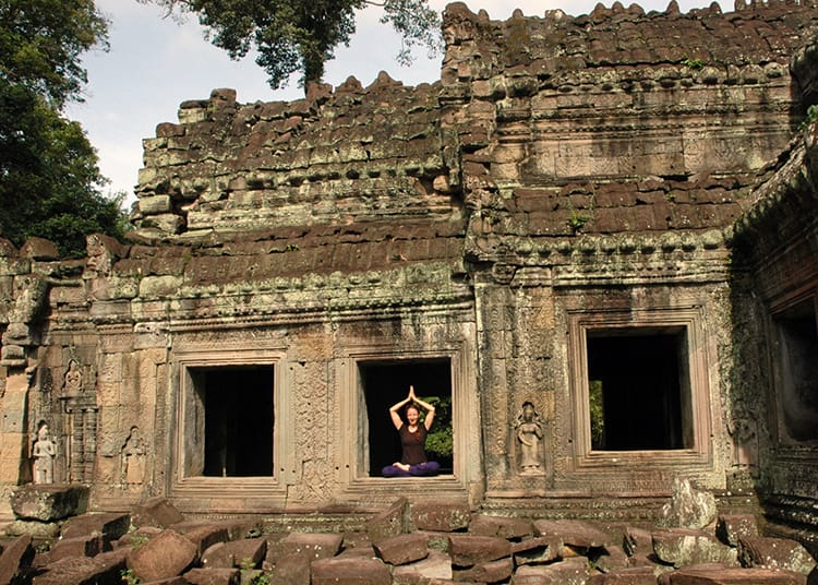 Michelle Della Giovanna from Full Time Explorer sits in the window of one of the stone temples in Angkor Wat
