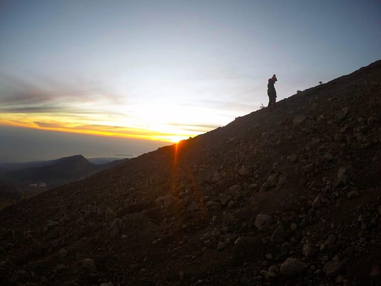 A single trekker climbs slowly up the dusty side of the volcano