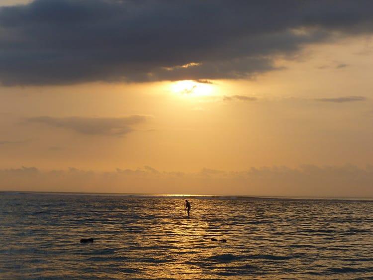 The sun setting over a paddle board in the ocean at Jungut Batu Beach in Nusa Lembongan