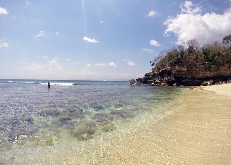 A few people splash in the water at Secret Mushroom Beach, one of Nusa Lembongan best beaches