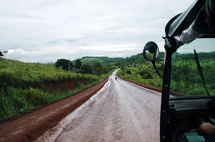 A tuk-tuk drives down a muddy road in Mondulkiri, Cambodia