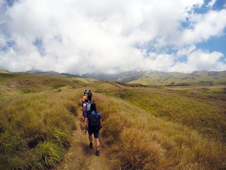 Trekkers walk through a field on the way to the base of Mount Rinajni