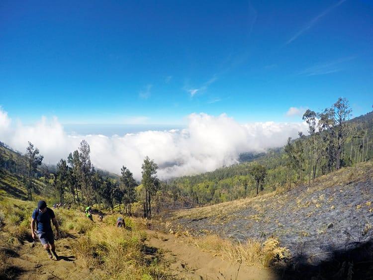Hiker climb a steep hill at the base of Mount Rinajni