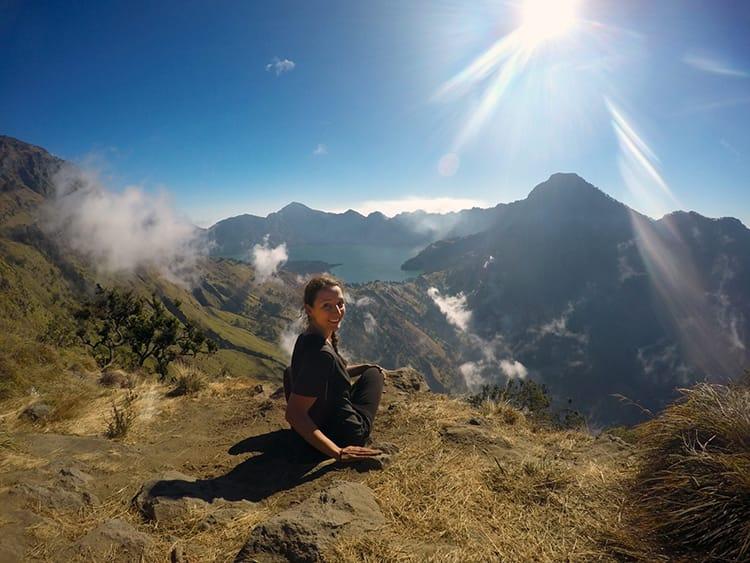 Michelle Della Giovanna from Full Time Explorer sits on the crater rim of Mount Rinajni