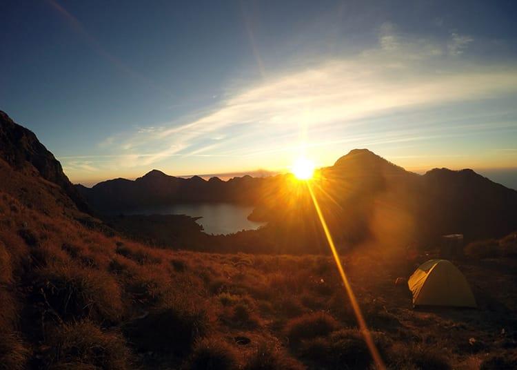 The sun sets over the crater rim of Mount Rinajni illuminating the mountains in orange