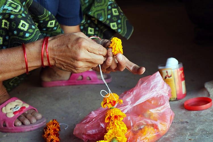 A woman threads marigold flowers into a garland for kukur tihar