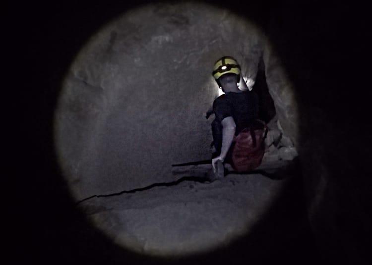 A man climbs through a small tunnel in a cave in Thailand