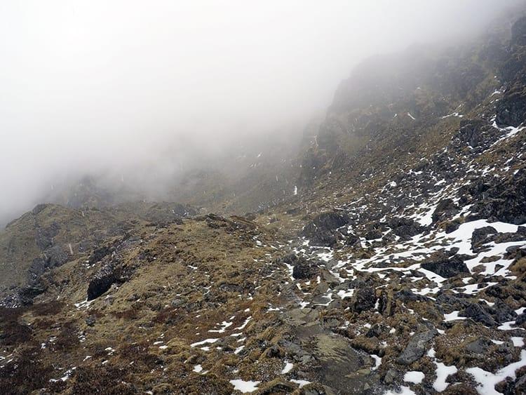 Snow falls on the rocky trail from Kothe to Thuli Kharka on the Mera Peak Trek