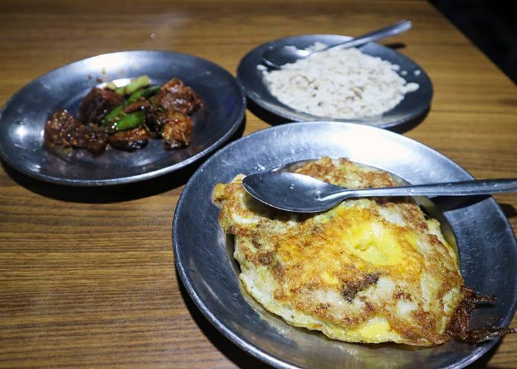 Local Newari food including bara, choila, and churra at Honacha restaurant in Patan