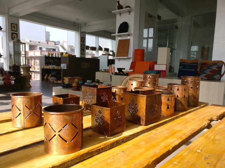 Handmade metal tea light candle holders line a shelf at KTM Haat