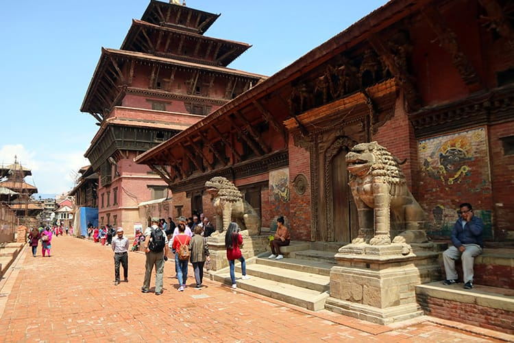 Tourists walk through Patan Durbar Square admiring the wood carvings