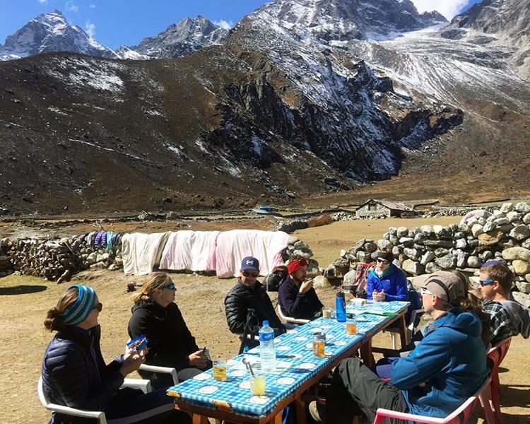 Trekkers having a tea break outside of a teahouse in Nepal