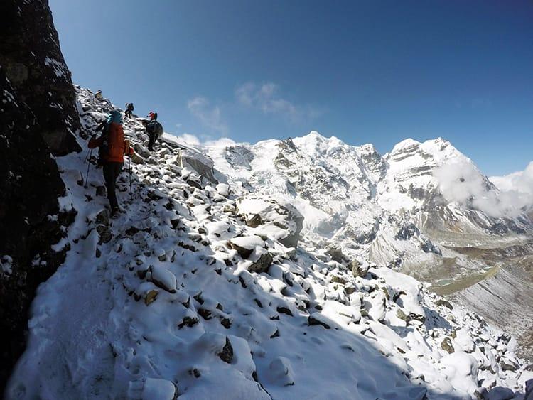 Trekkers climb to Mera Peak after snowfall along bumpy rocks