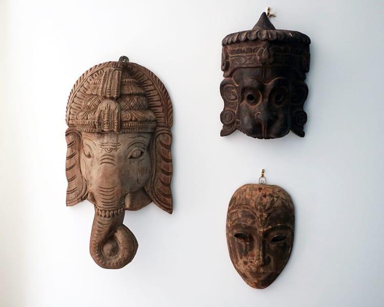 Three wood masks hung from the wall including Ganesh, Hanuman, and Buddha