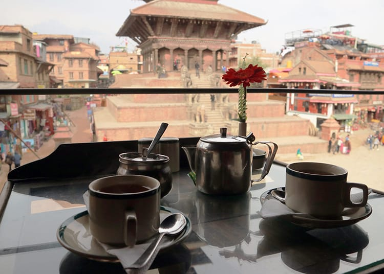 Hot tea being served in a small old temple in Bhaktapur that looks out at one of the famous squares full of beautiful architecture