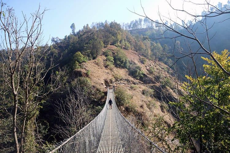 A trekker crosses a suspension bridge between Balthali and Panauti