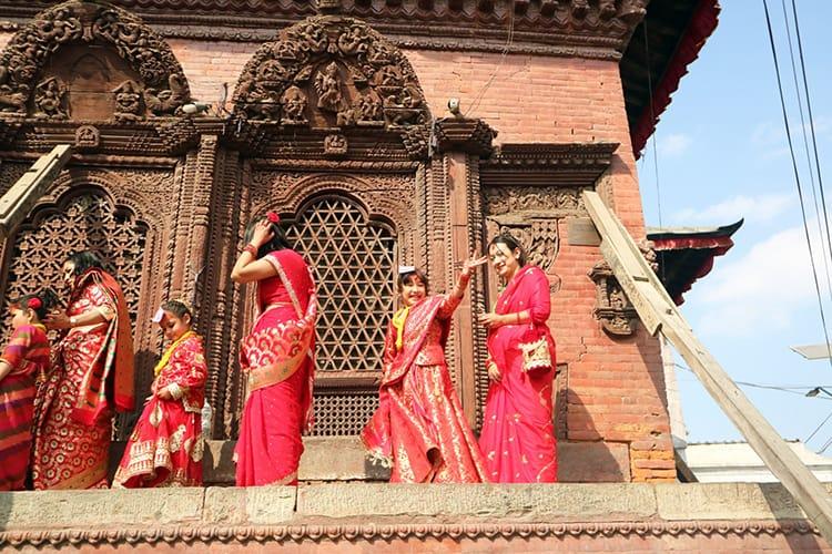 Girls walk around a temple in Kathmandu Durbar Square while waving to family below