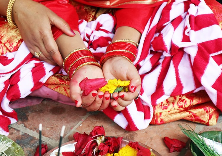 A young Nepali girl holds flowers in her hands during the Ehee puja