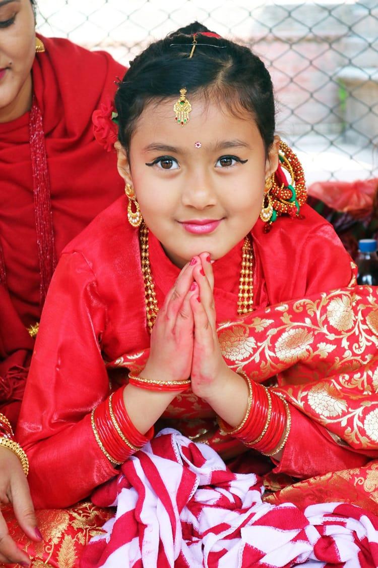A Nepali girl says namaste during the Ehee ceremony