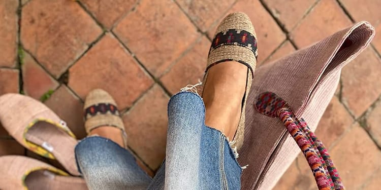 A women wears a pair of Paila shoes with a natural tan fiber and a black detail stripe across the toes