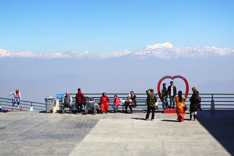 People stand in front of the viewpoint at Chandragiri Hills with a heart shaped sculpture