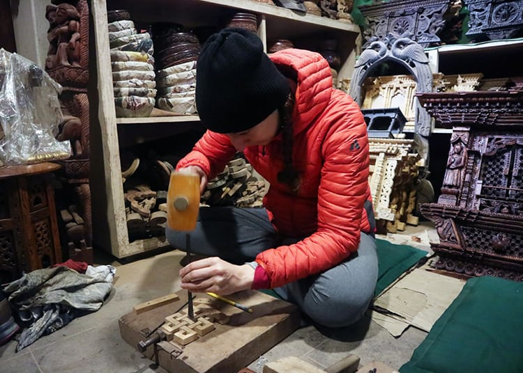 Michelle Della Giovanna of Full Time Explorer sits on the floor carving wood in a wood carving class
