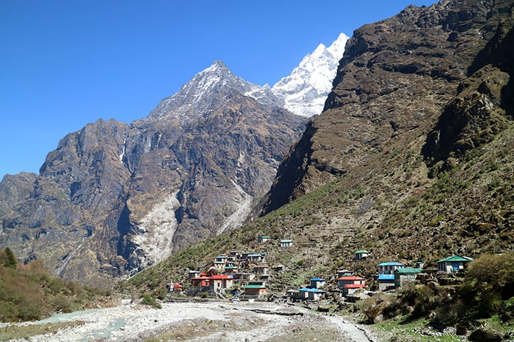 The little village of Beding, Nepal seen from afar with the Himalaya mountains overhead