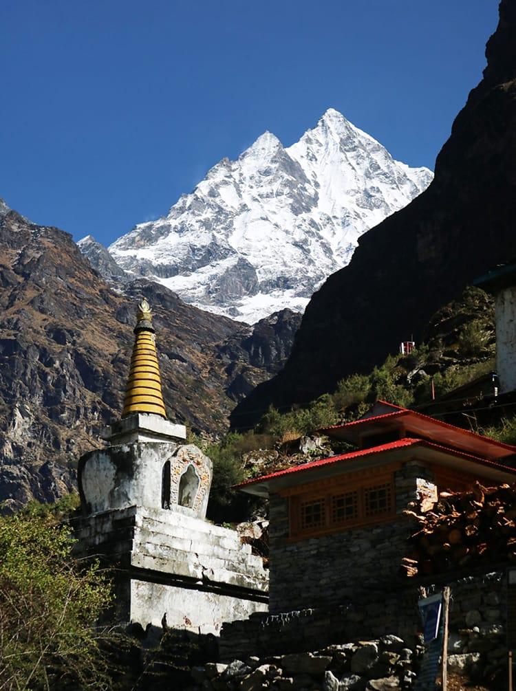 The bright white Himalaya mountains tower over a small Buddhist Stupa below