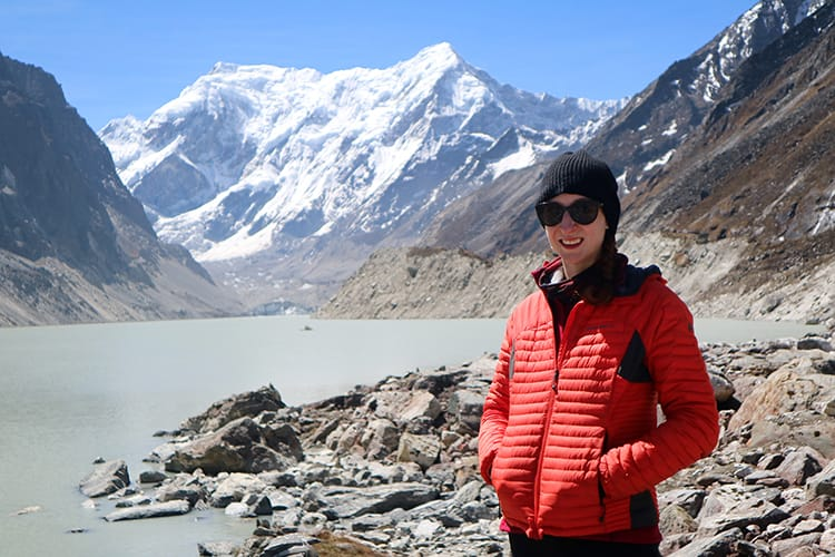 Michelle Della Giovanna from Full Time Explorer stands in front of Tsho Rolpa Lake wearing an Eddie Bauer Microtherm Coat