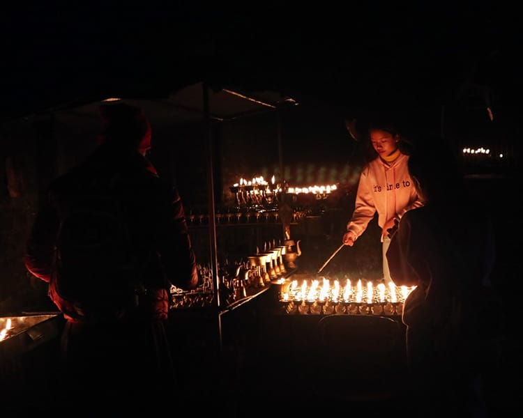 A girl lights candles outside on Boudhanath Stupa during Losar in Nepal in January