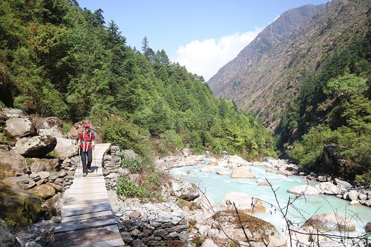 Michelle Della Giovanna from Full Time Explorer crosses a small wood bridge over a waterfall