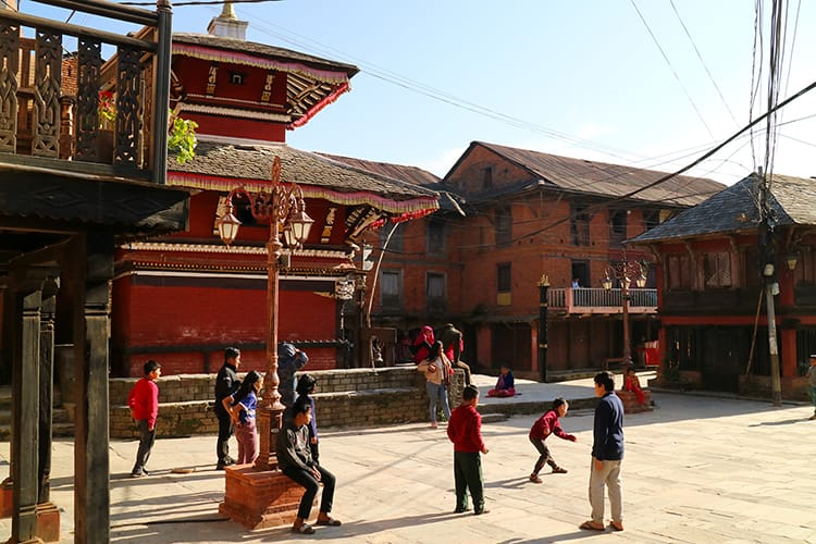 Children play a game of red light green light in front of a temple in Bandipur Bazaar