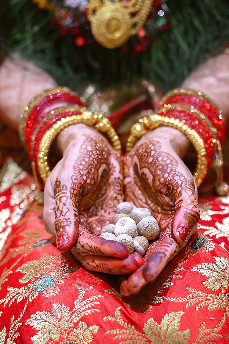 A bride holds betel nuts during a supari ceremony