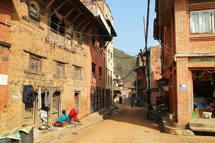 Women sit and chat on a street in Panauti, Nepal
