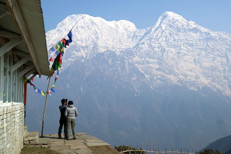 Two trekkers take pictures in front of the massive Annapurna Range at Mardi Himal High Camp