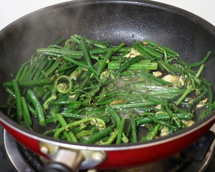 Fiddle head fern being sautéed in a pan